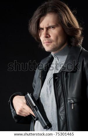 Man in leather wear holding gun. - stock photo