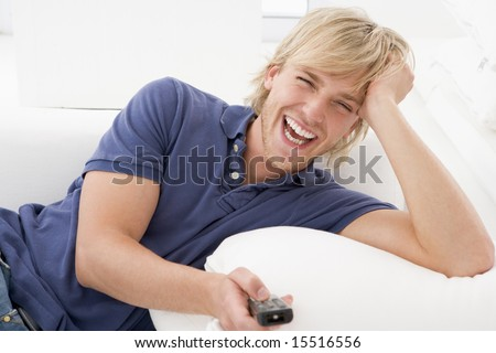 Man in living room holding remote control laughing - stock photo