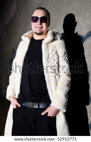Man in long white chinchilla fur coat posing like a pimp near the grungy  wall at night - stock photo
