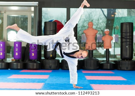 Man in martial art training in a gym, he is wearing a black belt - stock photo