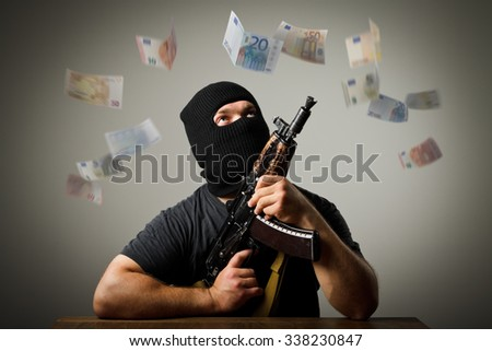 Man in mask with gun and falling euro banknotes. - stock photo