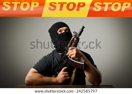 Man in mask with gun and STOP line over his head. Terrorism concept. - stock photo