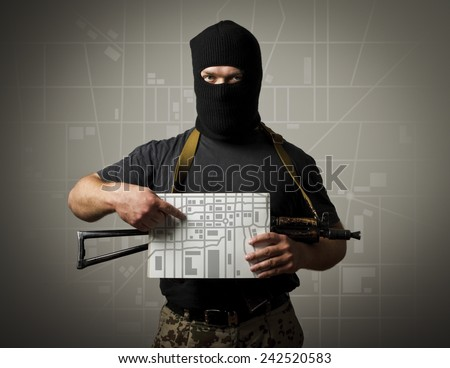 Man in mask with gun is holding a city map. Evacuation concept. - stock photo