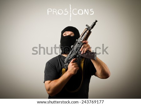 Man in mask with gun. Pros and cons concept. - stock photo