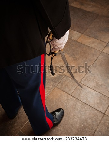 Man in military uniform with sword showing lower half of body only. - stock photo