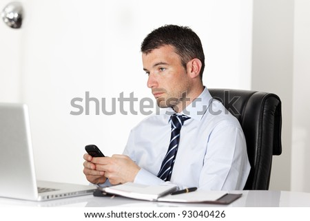 man in office with laptop sending a message - stock photo
