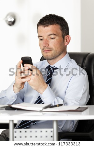 man in office with phone reading a message - stock photo
