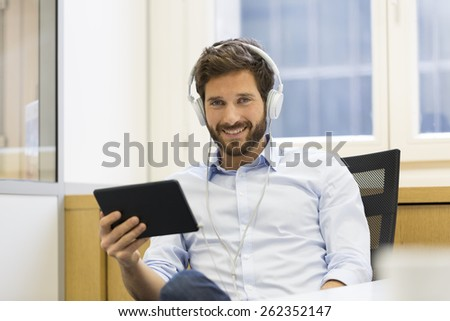 Man in office withe tablet pc and headphones. looking camera - stock photo