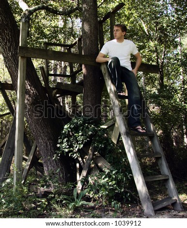 man in old treehouse - stock photo