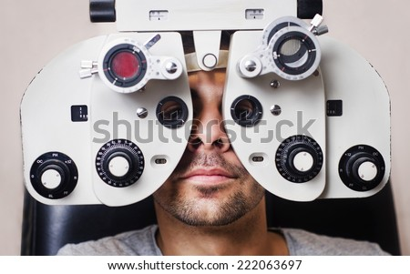 Man in optometrist phoropter ready for eye calibration, health care image. - stock photo