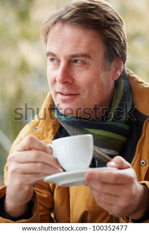 Man In Outdoor Caf���½ With Hot Drink  Wearing Winter Clothes - stock photo