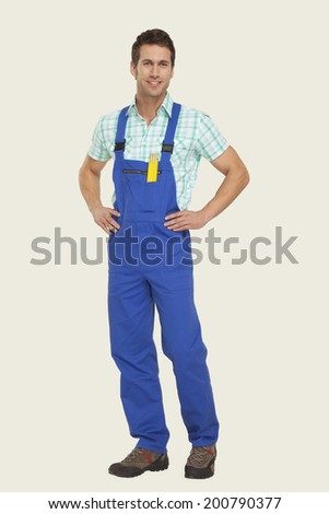 Man in overall standing with hand on hip - stock photo