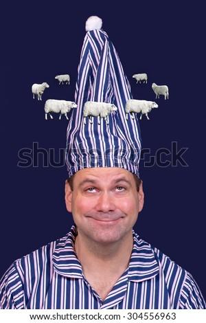 man in pajamas counts sheep - stock photo