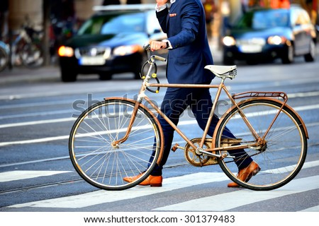 Man in perfect suit and old bike, typical Stockholm Scene - stock photo