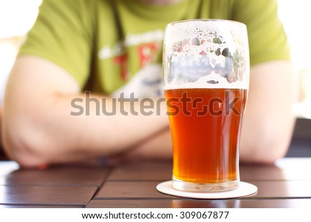 Man in pub sitting behind glass of tasty craft beer - stock photo