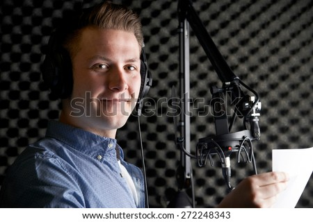 Man In Recording Studio Talking Into Microphone - stock photo