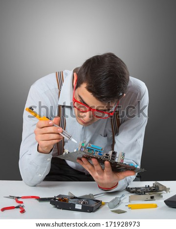 Man in red-framed glasses fixing a computer mother board, gray background - stock photo