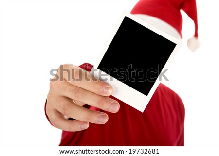 man in red shirt and santa hat holding a photo in front of his face - stock photo