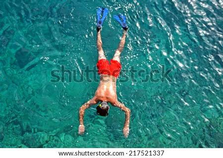 Man in red swimwear snorkeling in the sea - stock photo