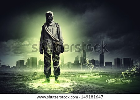 Man in respirator against nuclear background touching symbol. Pollution concept - stock photo