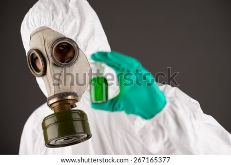 Man in respirator and protective clothing showing a beaker with green liquid - stock photo