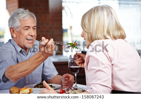 Man in restaurant letting his woman taste from his food - stock photo