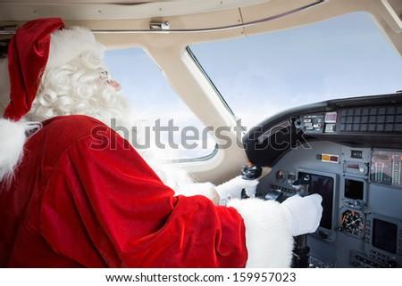 Man in Santa costume holding control wheel in cockpit of private jet - stock photo