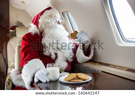 Man in Santa costume holding cookie while looking through private jet's window - stock photo