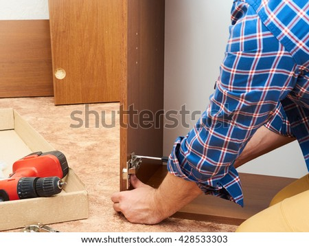 Man in shirt assemble furniture. Domestic work. Craftsman. Carpenter.   - stock photo