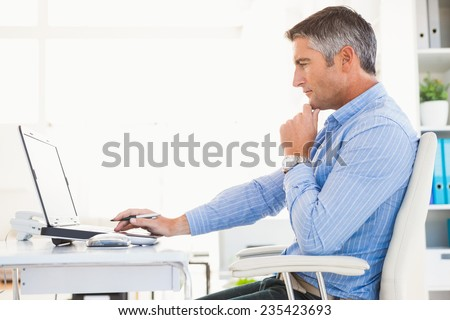 Man in shirt using laptop and thinking in his office - stock photo