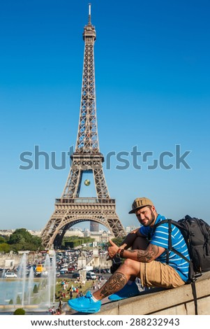 Man in shorts and blue shirt sitting on parapet near Eiffel tower - stock photo