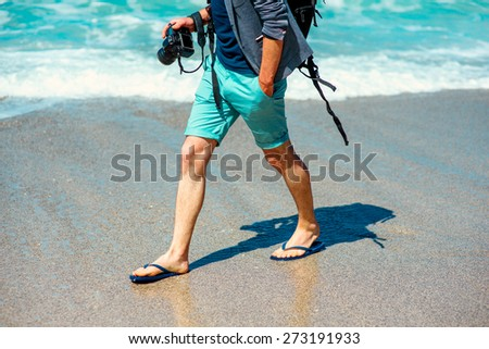 Man in shorts walking with photo camera on the beach - stock photo