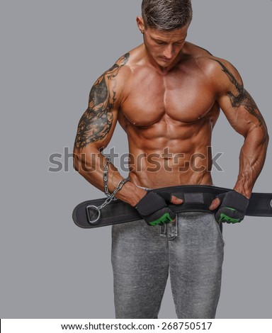 man in shorts with naked muscular torso holding power waist. Isolated on grey - stock photo