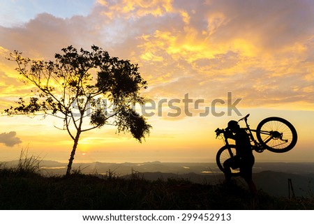 Man in silhouette holding a mountain bike over his shoulder with sunset background.  - stock photo