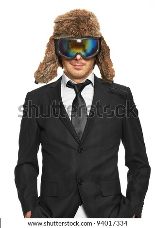 Man in ski goggles and black suit standing, isolated on white background - stock photo