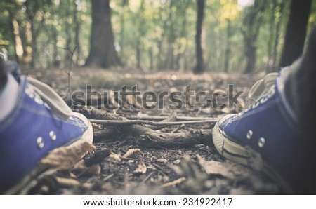 Man in sneakers in the forest   - stock photo