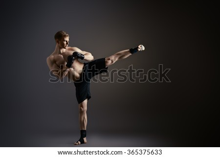Man in sportswear performing a kick. Martial arts. Studio shot. - stock photo
