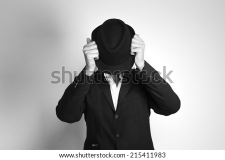 Man in suit and black hat at the age of forty-six years old lcovers his face with a hat on the background of a rough wall with texture - stock photo