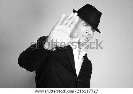 Man in suit and black hat at the age of forty-six years old with his eyes closed on the background of a rough wall with texture - stock photo
