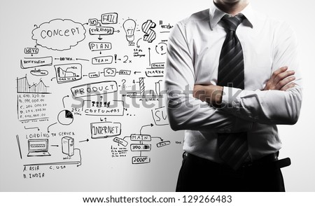 man in suit and business plan on wall - stock photo