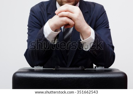 Man in suit and tie with hands on huge black suitcase - stock photo