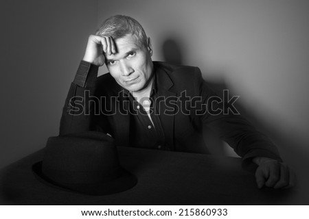 Man in suit at the age of forty-six years old  with hand to head support  looking at the camera on the background of a rough wall with texture - stock photo