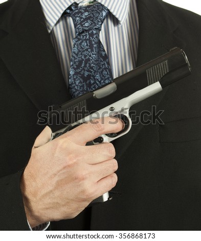 Man in suit carries a gun - stock photo