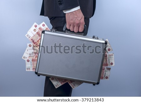 Man in suit carrying a metal briefcase with russian rubles. Conception of safe storage and protection of cash. Financial theme. Horizontal view. - stock photo