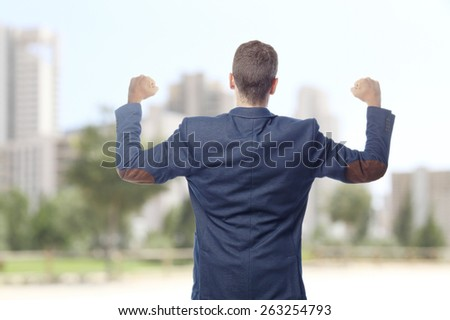 Man in suit celebrating back in a city - stock photo