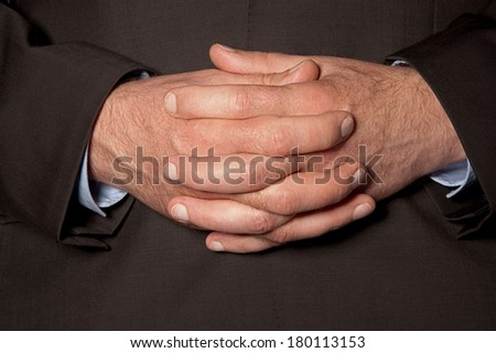 Man in suit clasped fingers in front of him closeup - stock photo