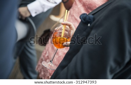 Man in suit holding a cocktail glass - stock photo