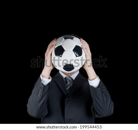 Man in suit holding ball in front of his face. Football   - stock photo
