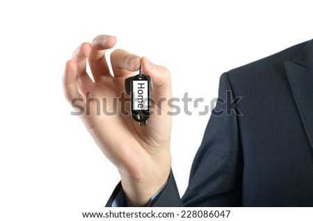 man in suit holding key to new home in hand on white background  - stock photo