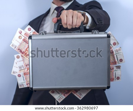Man in suit holds metal briefcase full of money - stock photo